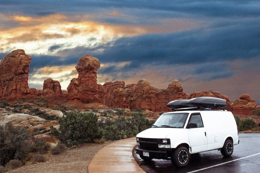 A van rests in a parking space in front of red rocks cutting into the skyline on a road trip