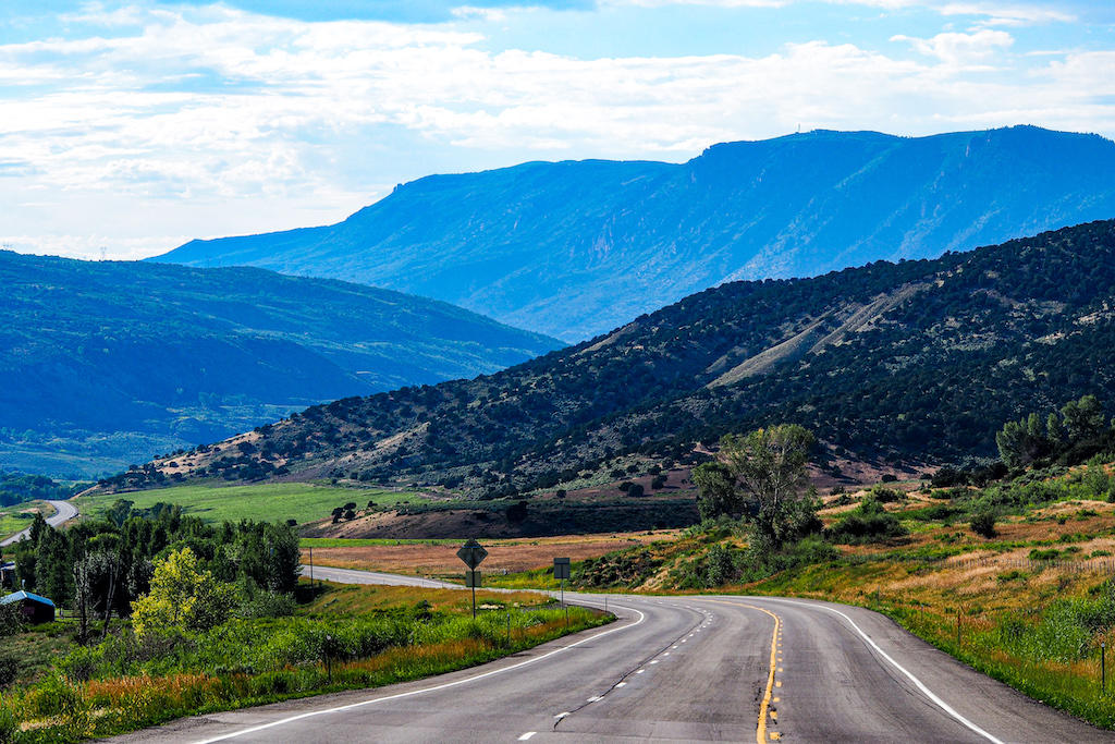 A winding open road leading towards mountains in the distance