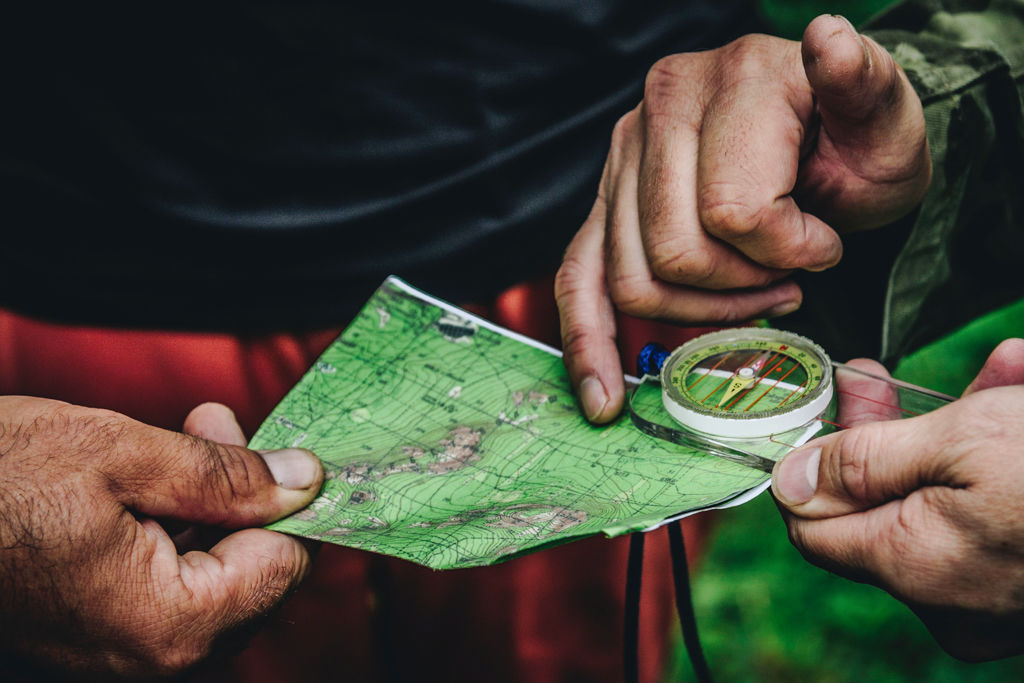 Two day hikers look at a map while navigating their way along the trail