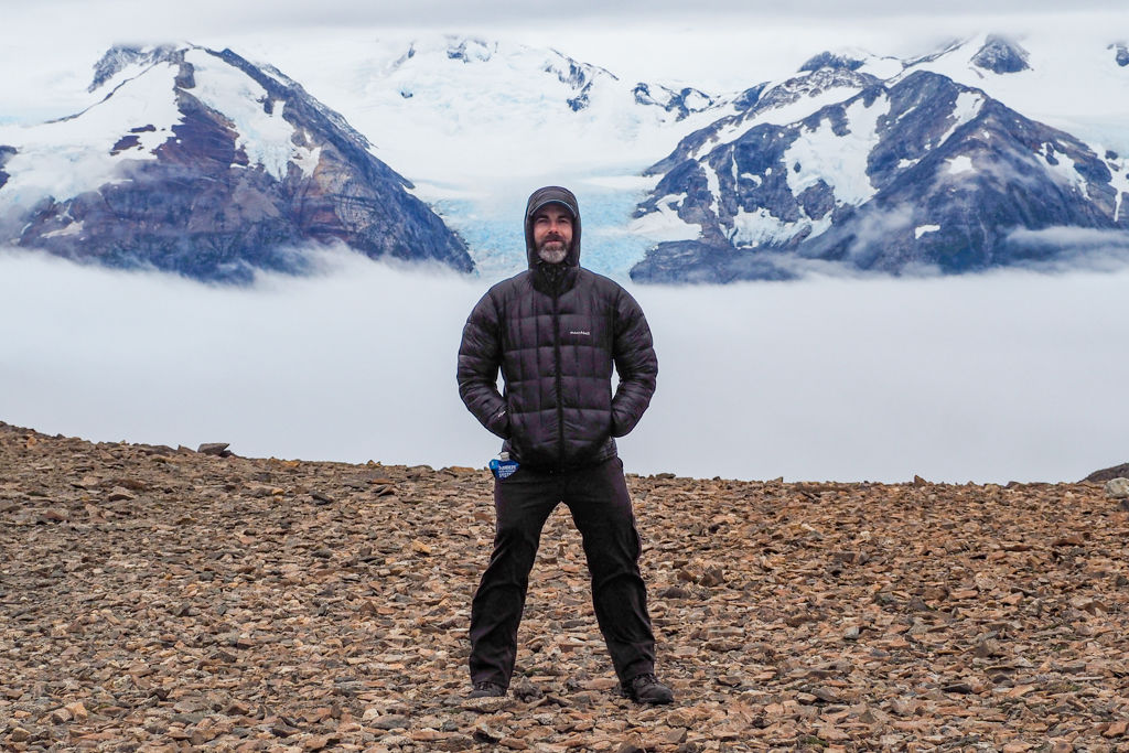 A man in a packable down jacket stands in front of a foggy glacial field