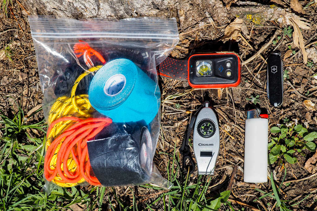 A head lamp, pocket knife, lighter, compass, whistle, rope, tape, and other emergency gear for day hiking