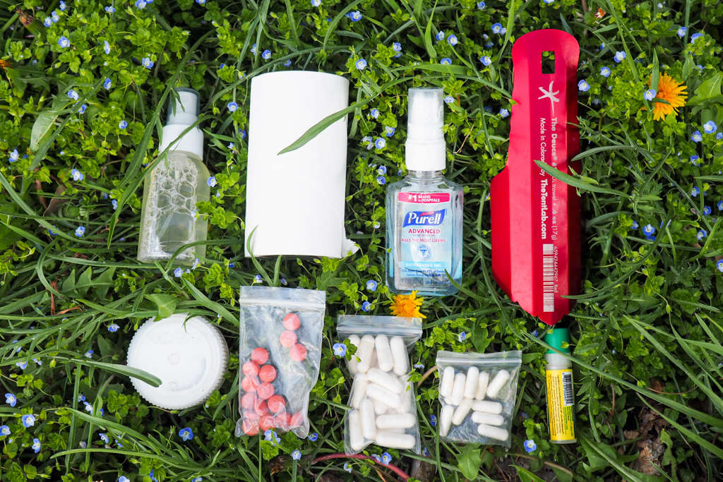 A trowel, toilet paper, hand sanitizer, bug spray, sunscreen, medication, and lip balm part of a backpackers toiletries kit