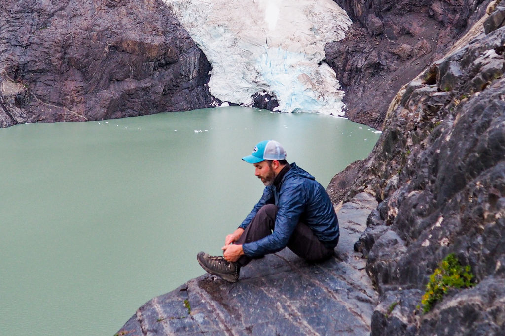 An ultralight backpacker ties his shoes in front of a glacial lake