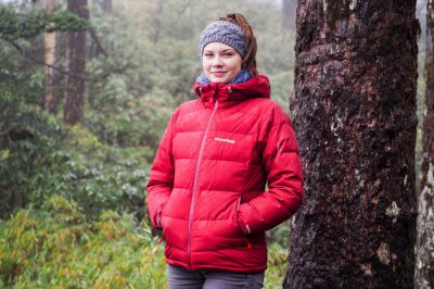 Woman standing in the forest with a smile wearing a red down jacket
