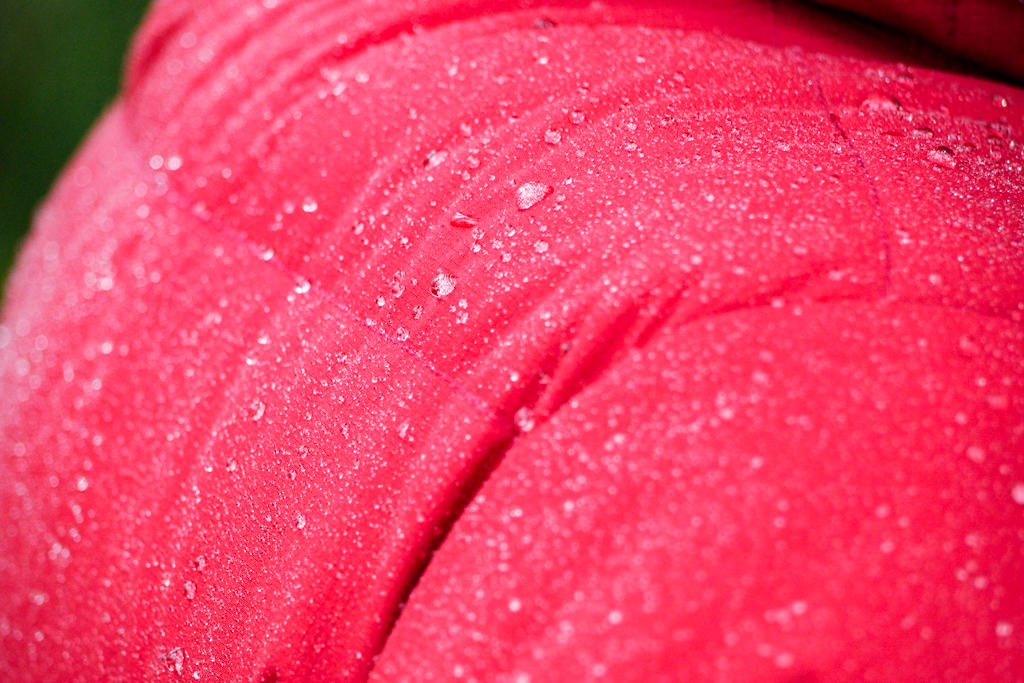 Beads of water running down the back of a red down jacket