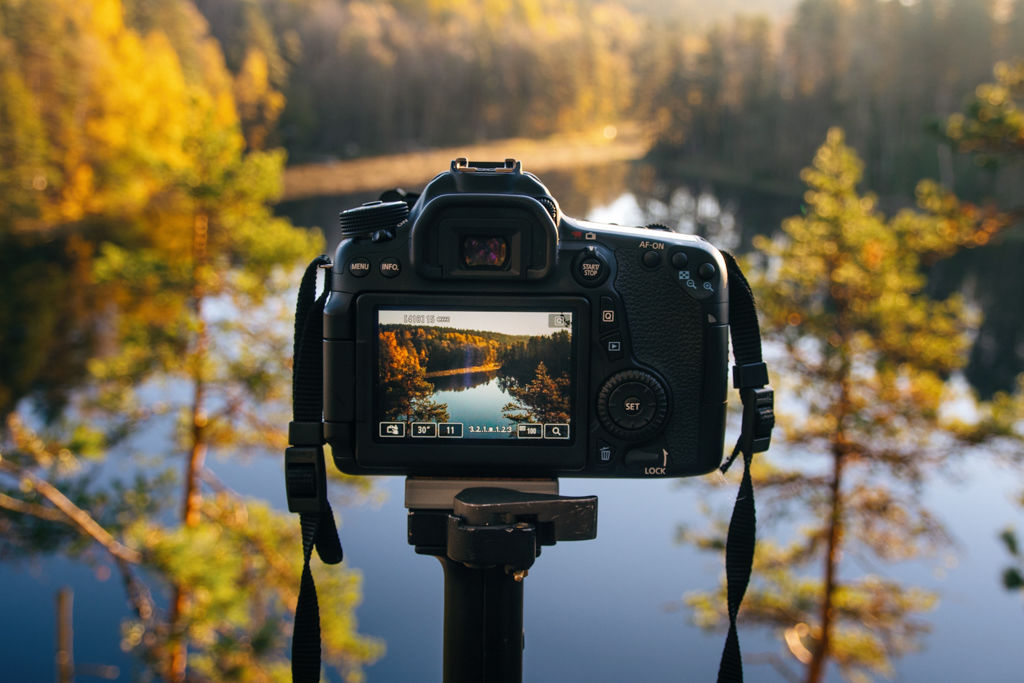 A camera on a tripod pointed at a mountain lake with pine trees in the distance