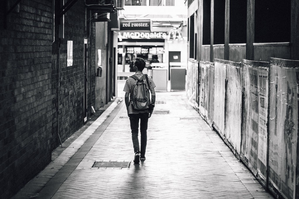 Man walks down an alley with a lightweight travel backpack in black and white