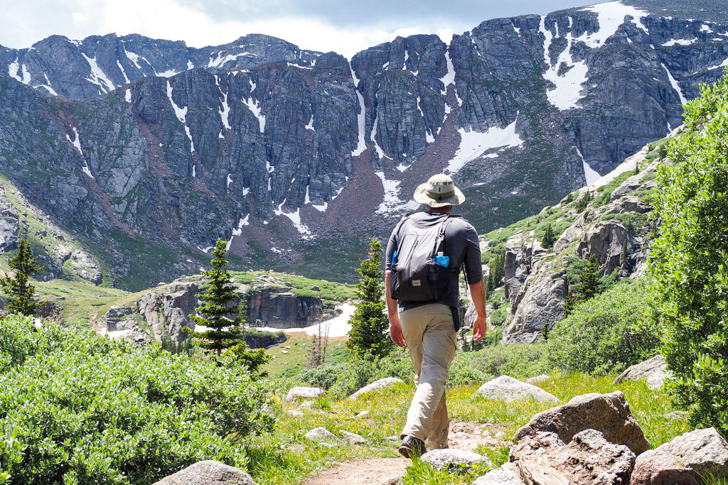 A man day hikes towards mountains with a day pack full of hiking essentials