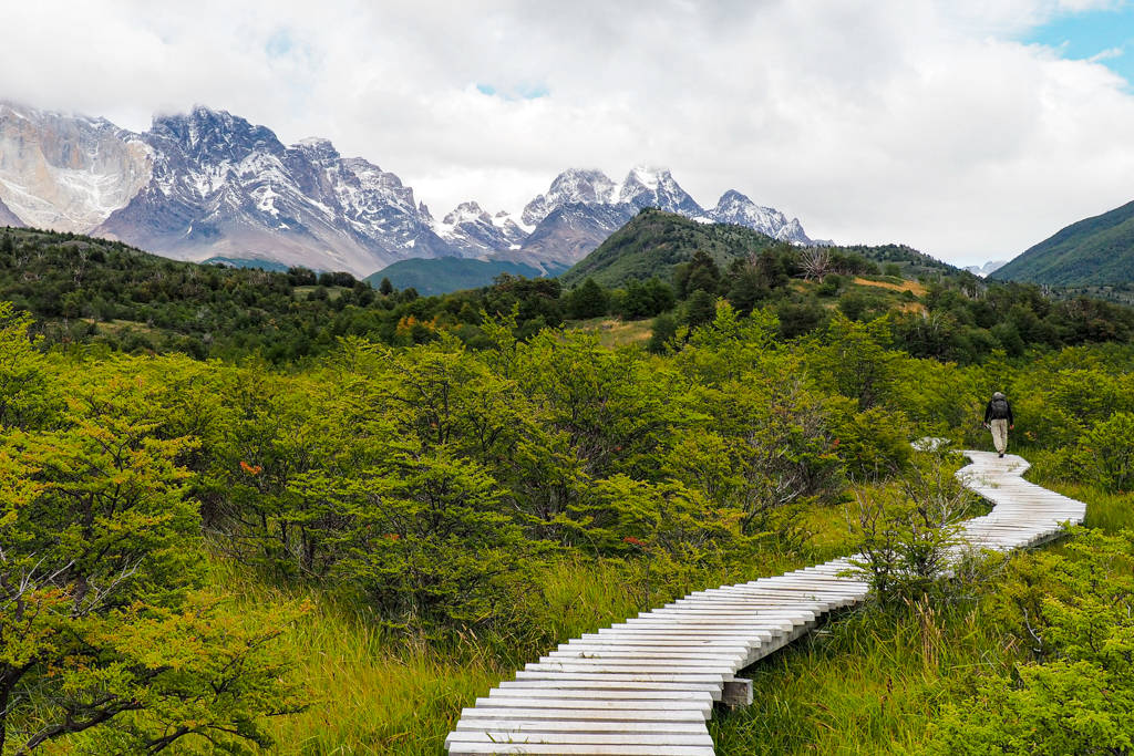 A man day hiking down a wooden bridge towards mountains in the distance