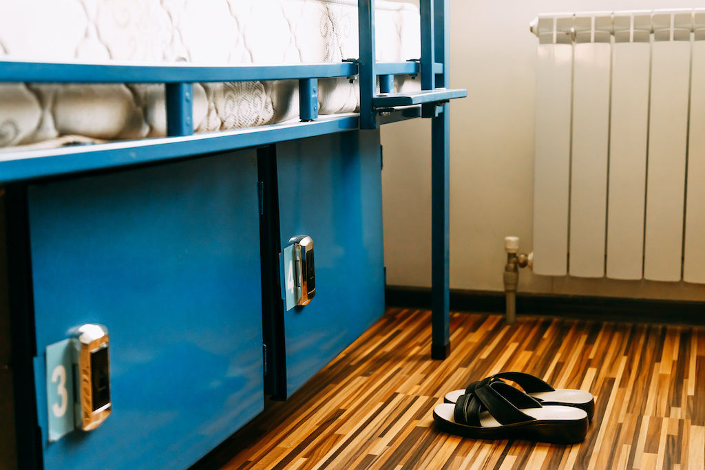 Hostel dorm room with sandals on the floor next to two lockers