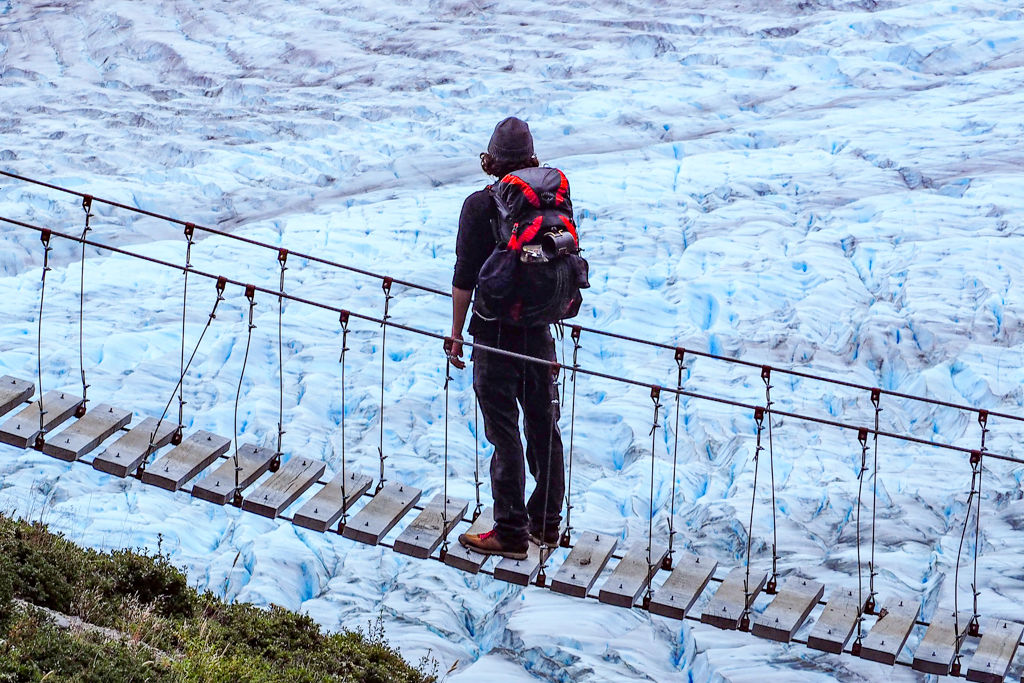 A man crossing a bridge in front of a glacier wearing an ultralight backpack