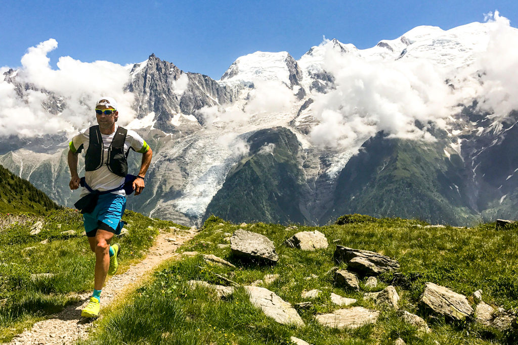 A man trail running with snow-capped mountains in the background