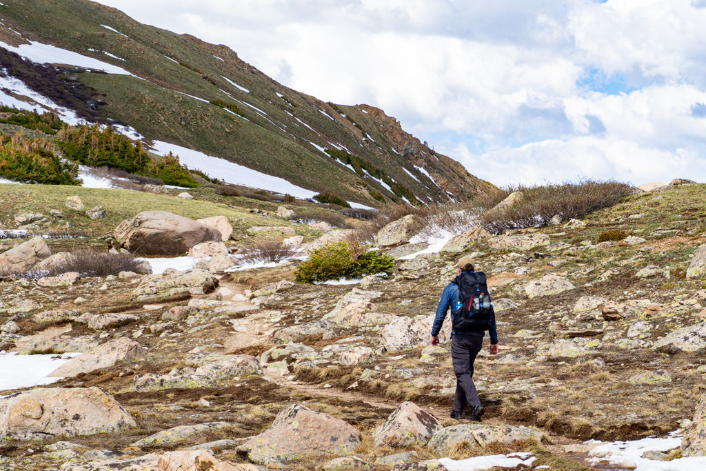 A hiker walking down the Herman Gulch Trail in the Arapaho National Forest of Colorado