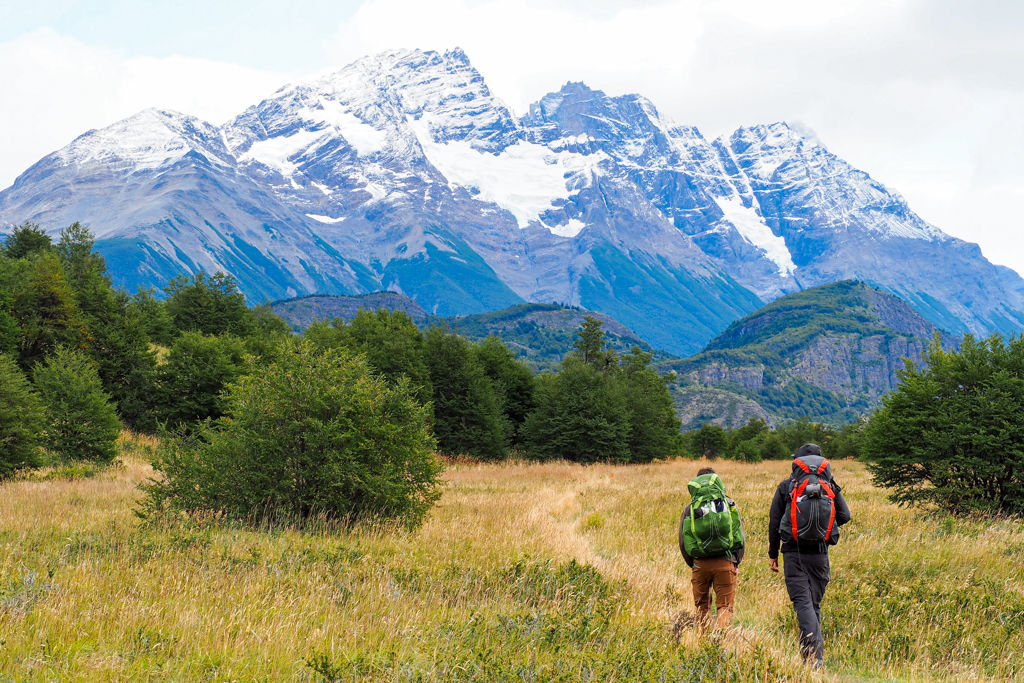 Two hikers walking down a trail towards snowcapped Patagonian mountains