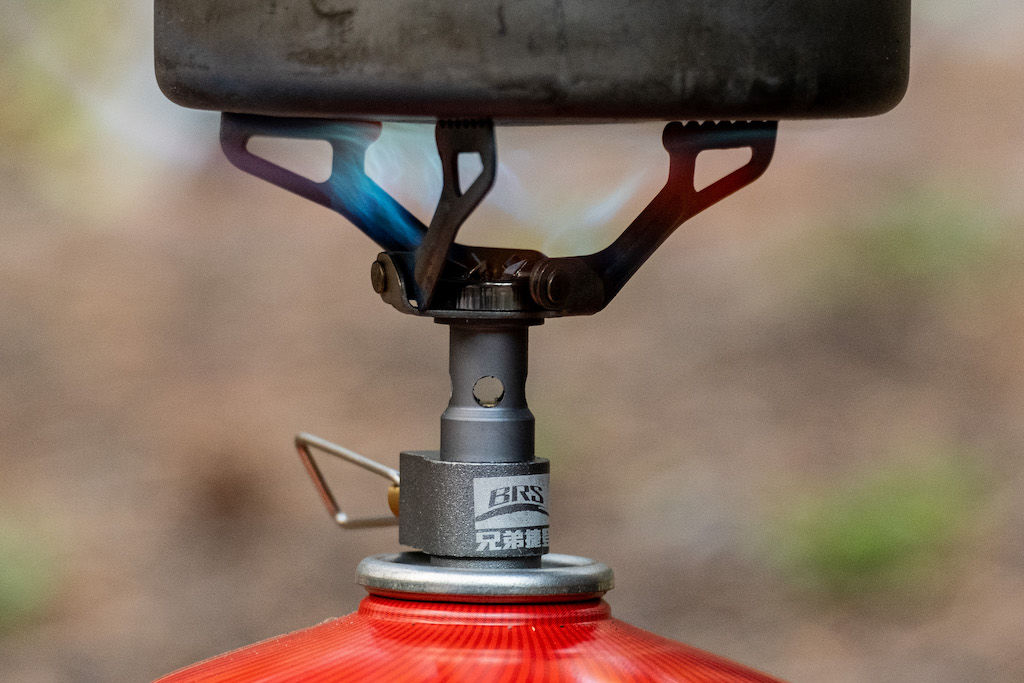 A backpacking stove cranking out a flame while boiling water