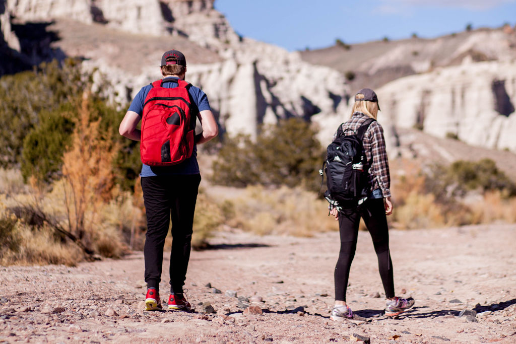 Man and a woman hiking down a gravel trail together