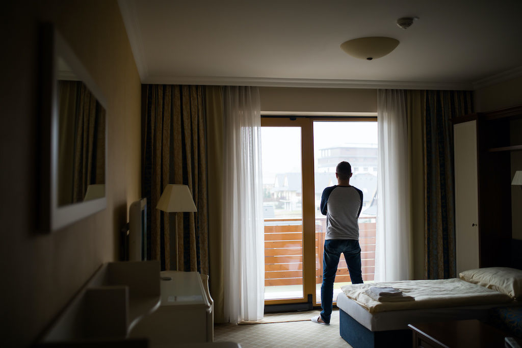 Man looking out of his hotel room contemplatively