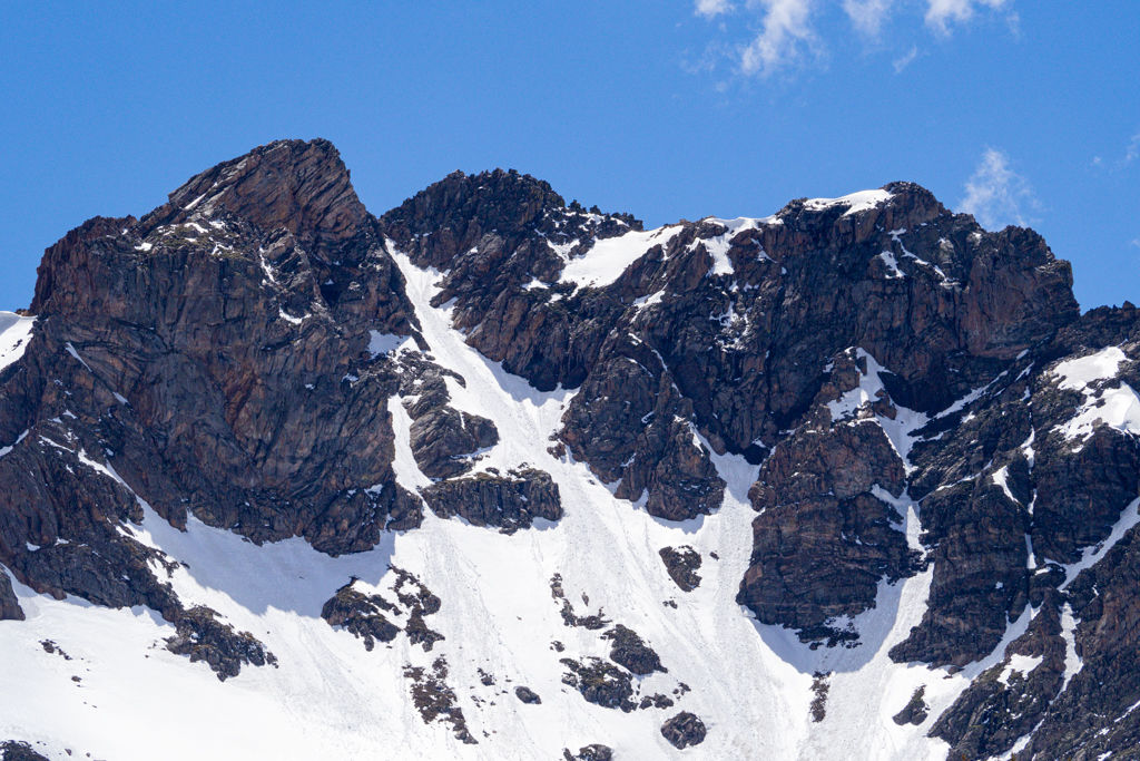 The towering Pettingell Peak and  covered in snow against a blue sky