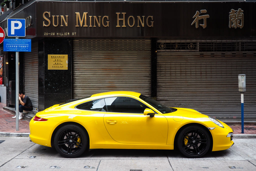 A yellow Porsche parked in the streets of Hong Kong