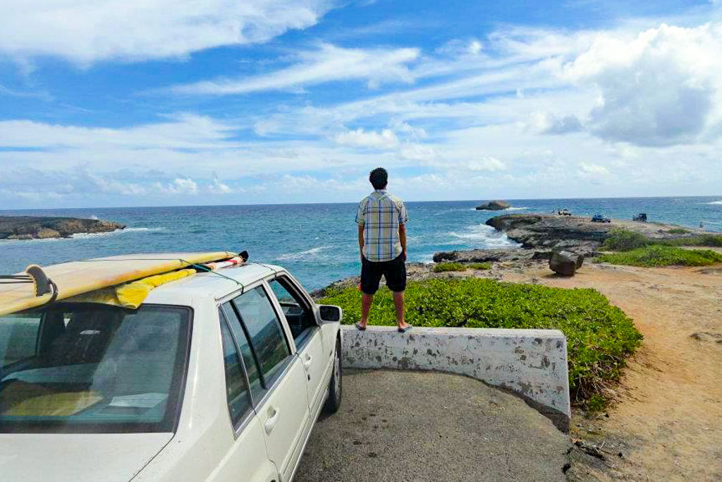 A man standing in front of his car looking over the ocean on a road trip of Hawaii