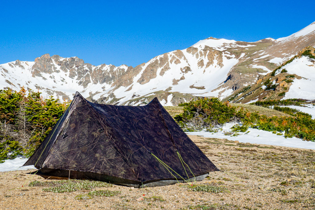 A camo ultralight backpacking tent with a mountain range and blue sky in the distance