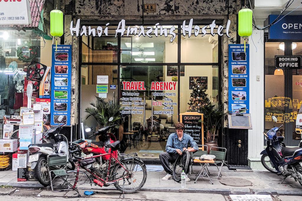 Man fixing a bike in front of a hostel in Hanoi, Vietnam