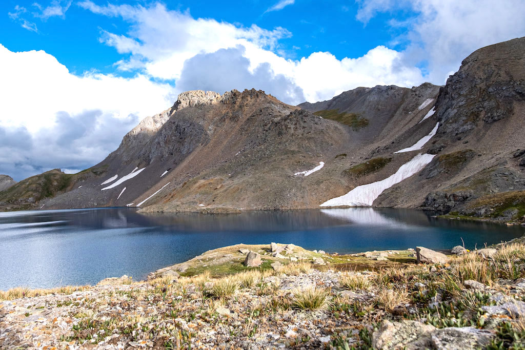 Columbine Lake against a backdrop of mountains and clouds against a bright blue sky