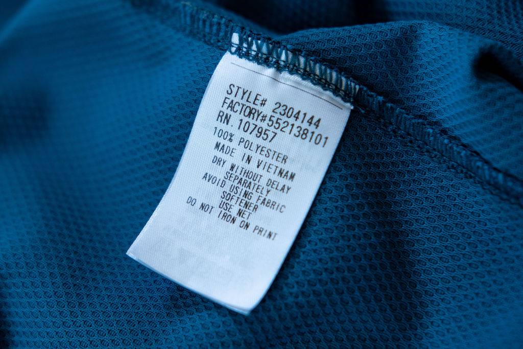Up-close photo of blue polyester material with a tag