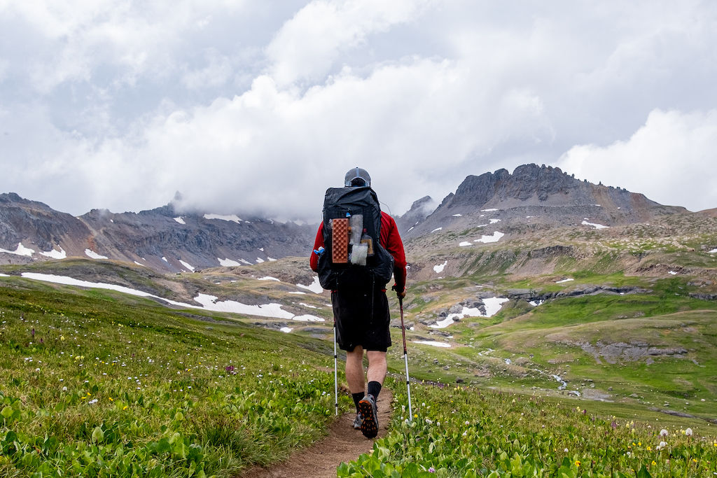 An ultralight backpacker hiking towards mountains with fluffy clouds hanging overhead