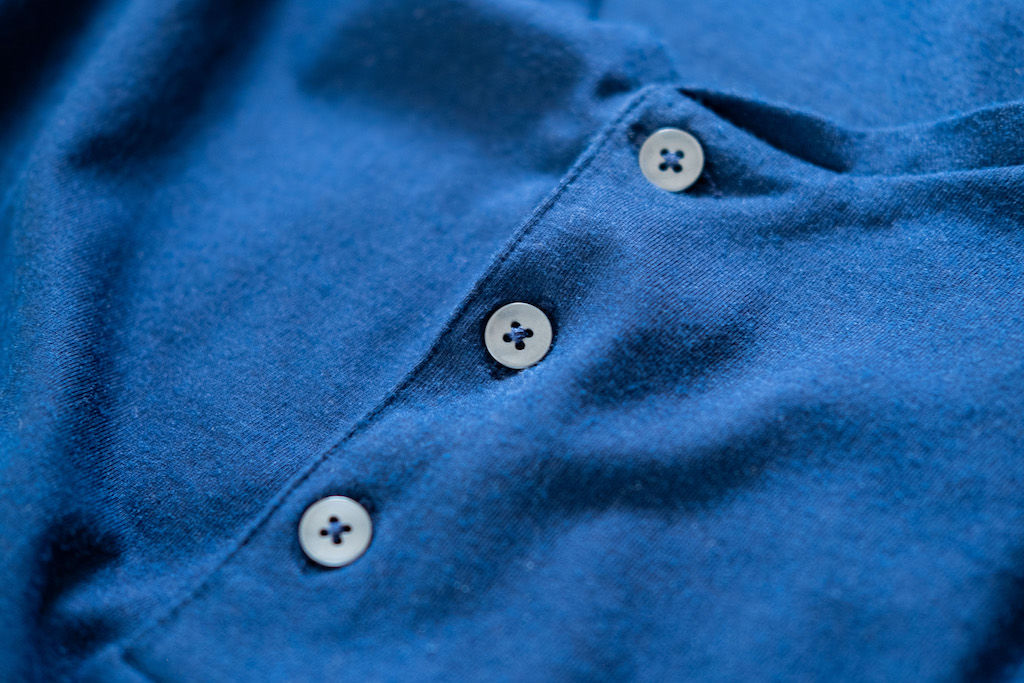 Photo of three buttons on a blue shirt made of a cotton vs polyester blend