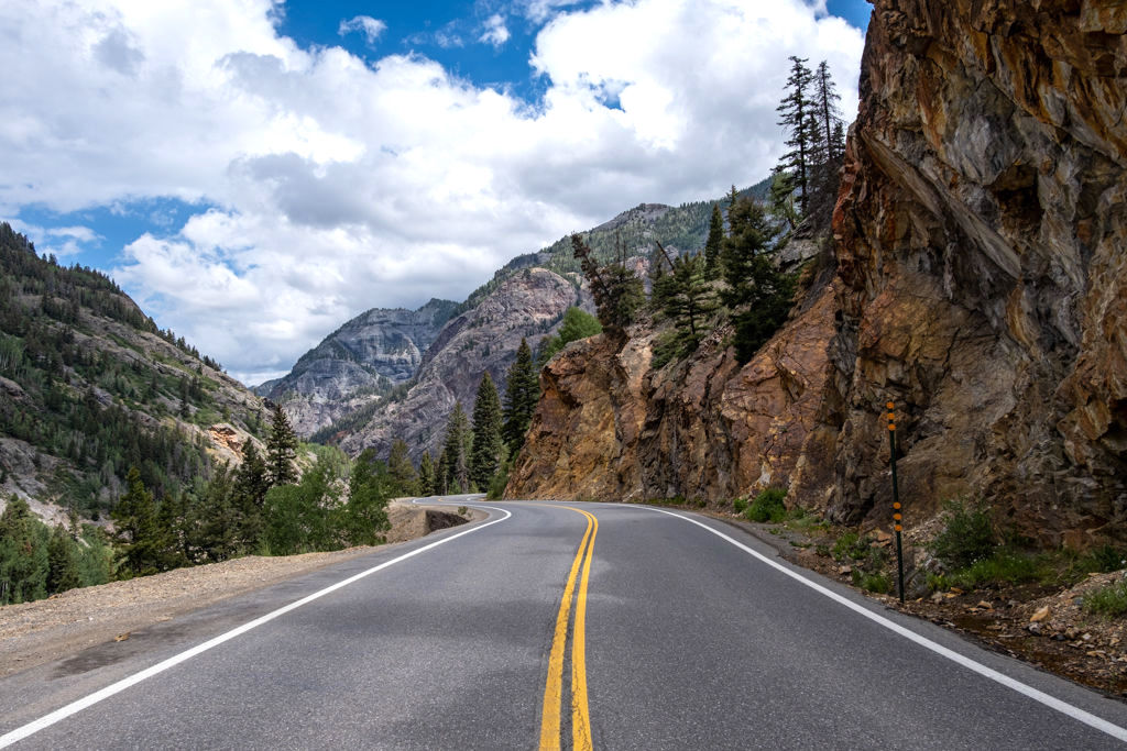 A winding mountain road during a trip through southwestern Colorado against a cloudy sky