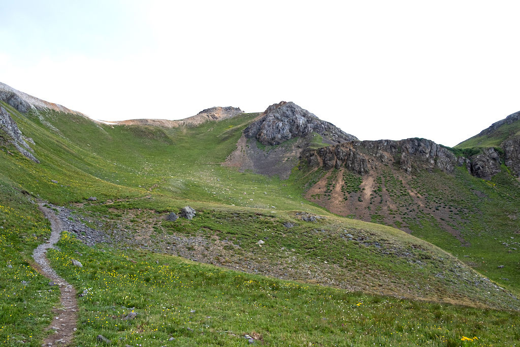 A hiking trail winds uphill towards a saddle with overcast skies above