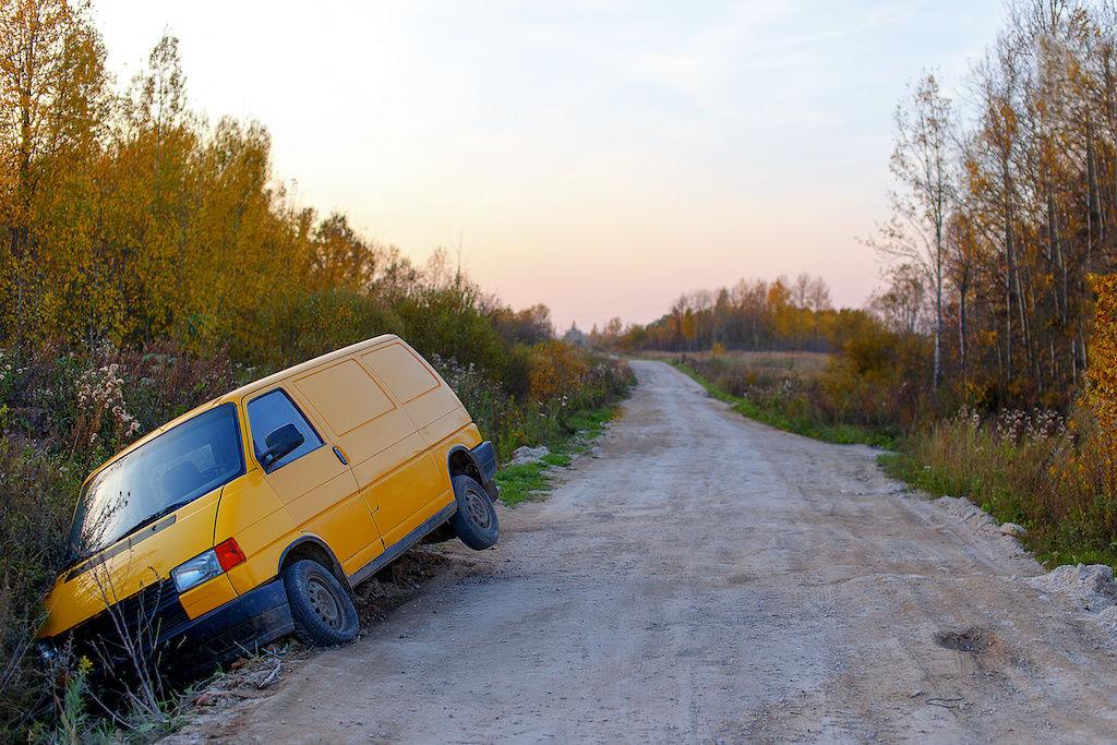 Orange camper van that has slid into a ditch on a dirt road