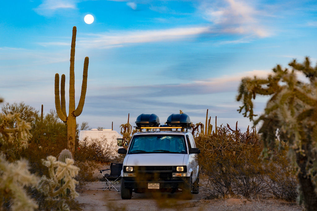 A white camper van in a BLM desert campsite in Southern Arizona during van life