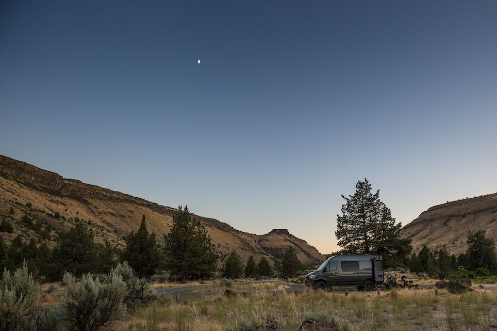 Mercedes Sprinter van in a meadow campsite before sunset with the moon in the sky