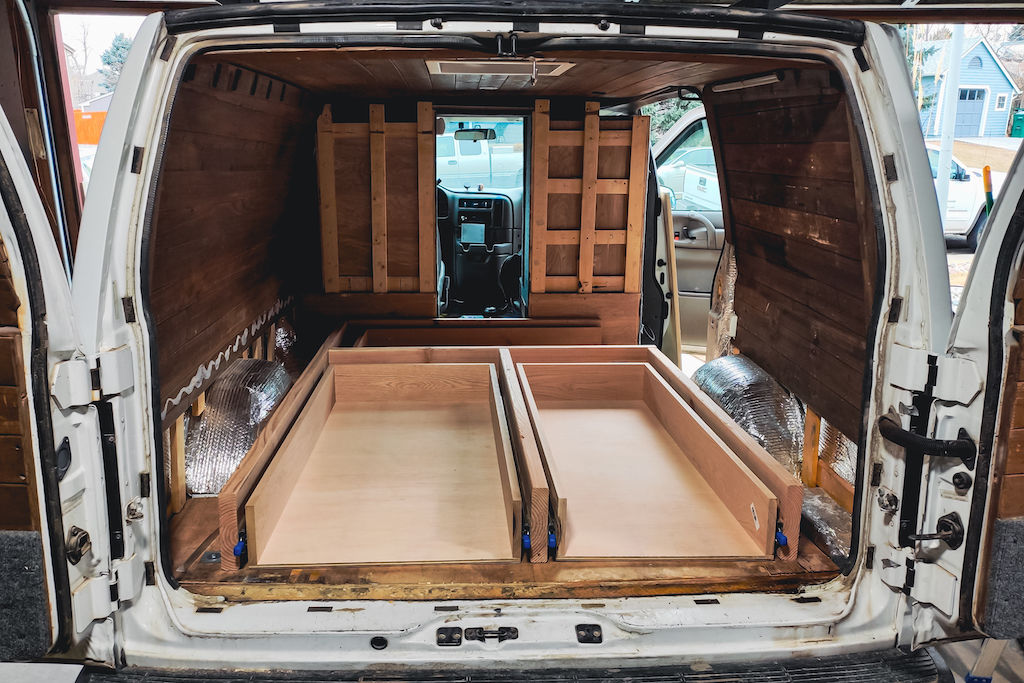 White camper van with back doors open while building drawers during van life conversion