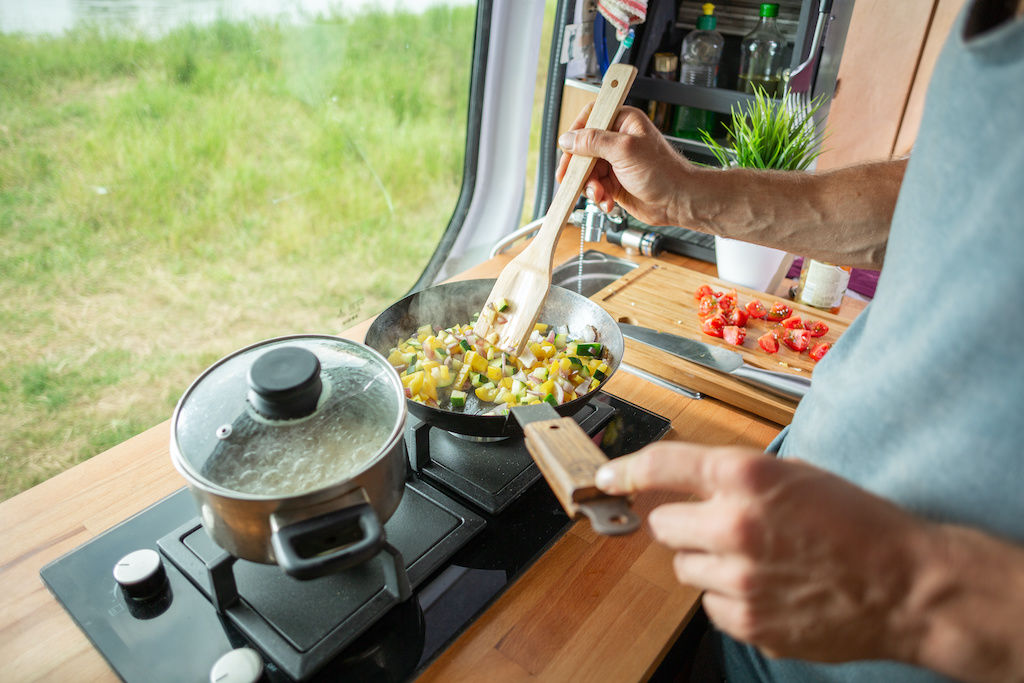 Man cooking a meal on a two-burner stove inside his converted camper van