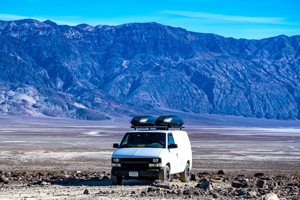 White conversion van for van life in front of a mountain range in Death Valley, California
