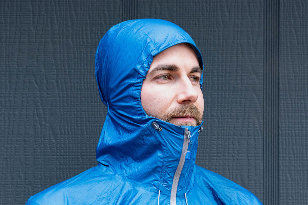 Man in a blue rain jacket with hood tightened around his face