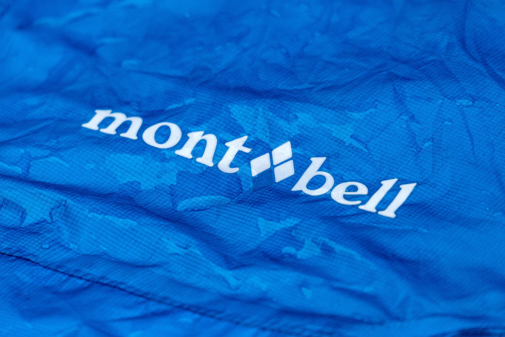A blue rain jacket with water over a Montbell logo