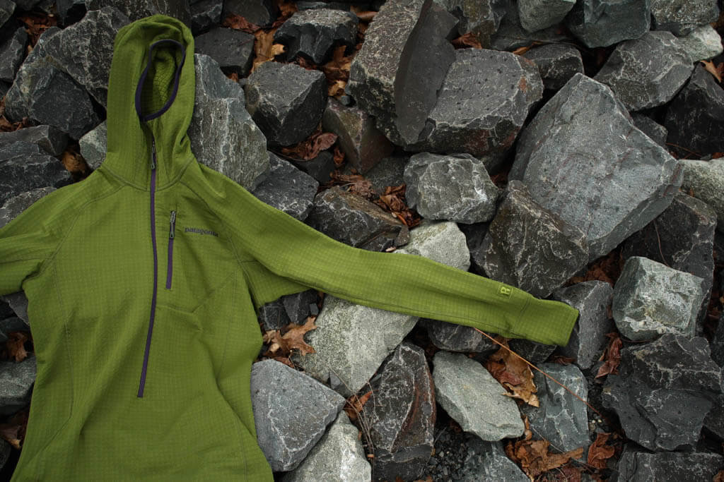 Green activewear midlayer hoodie laid out over a bed of rocks