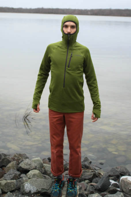 Backpacker wearing a green pullover fleece with the hood pulled up