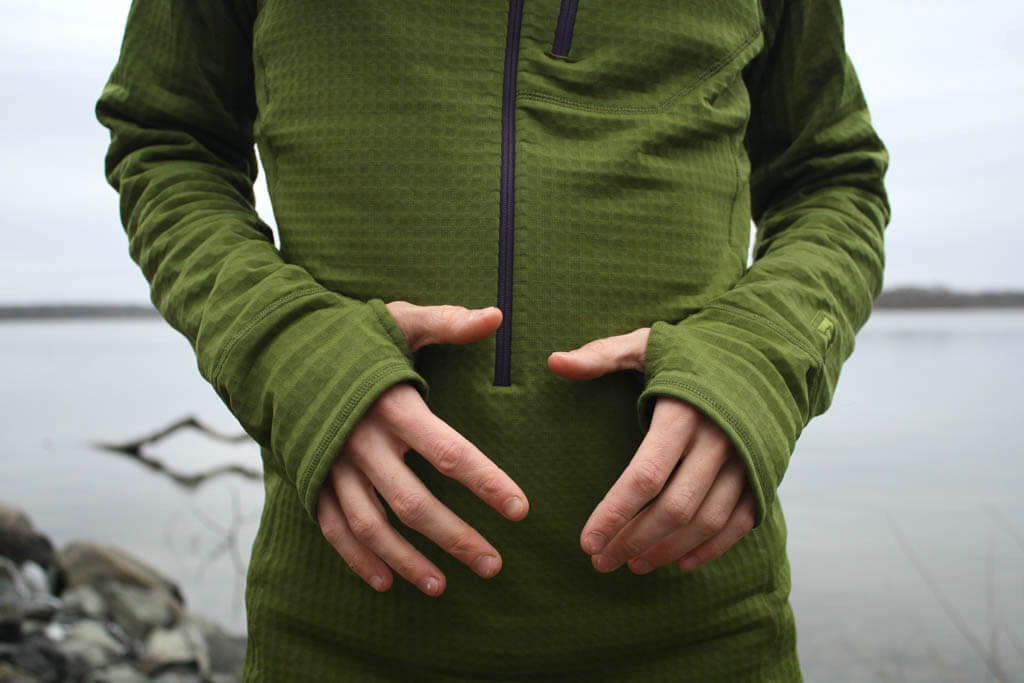 Man wearing a green pullover fleece with thumb loops