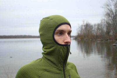 Hiker wearing a green pullover fleece balaclava style hoodie