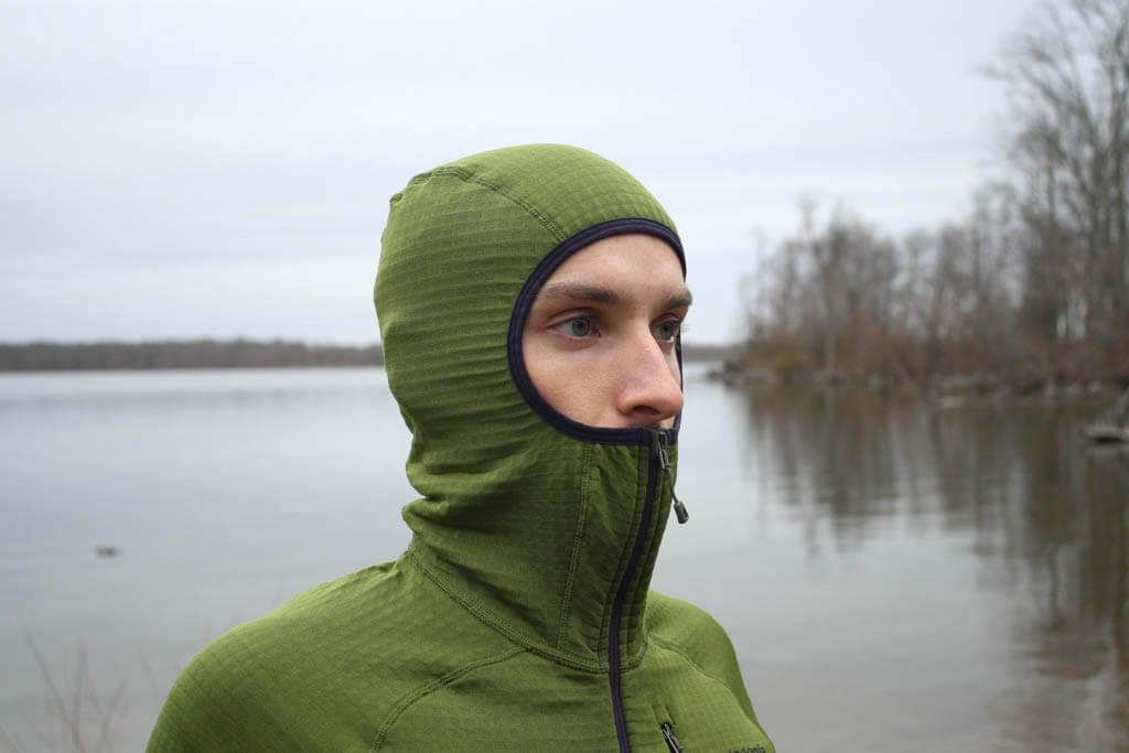 Hiker wearing a green pullover fleece balaclava style hoodie