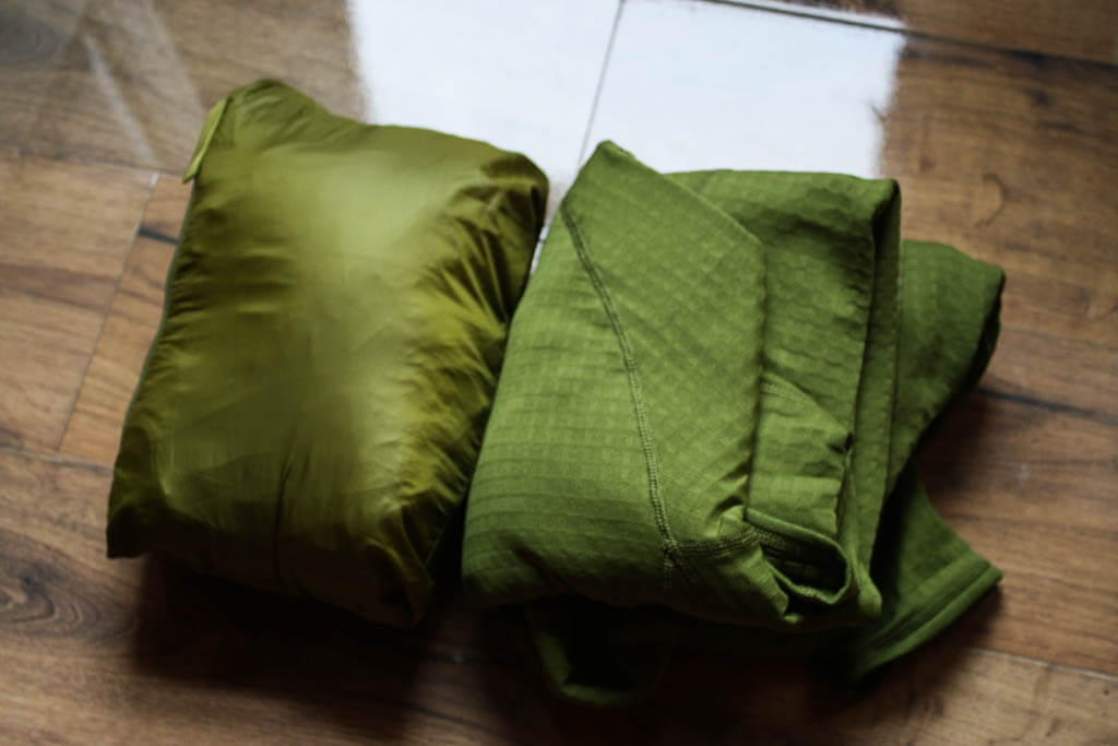 Folded up hiking/backpacking fleece next to a filled stuff sack