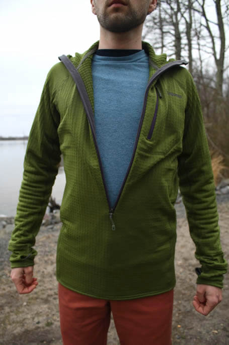 Man wearing a green Patagonia R1 Regulator Pullover Hoodie with the zipper completely unzipped